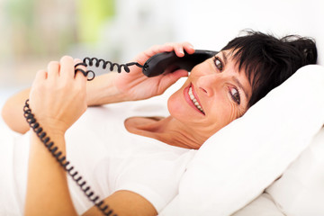 middle aged woman lying on bed and talking on landline phone