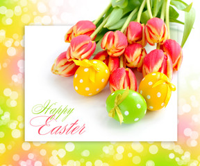Easter eggs with tulips on festive background with space for tex