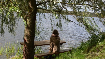woman girl sit wooden bench willow tree move wind lake relax