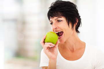 healthy middle aged woman eating a green apple
