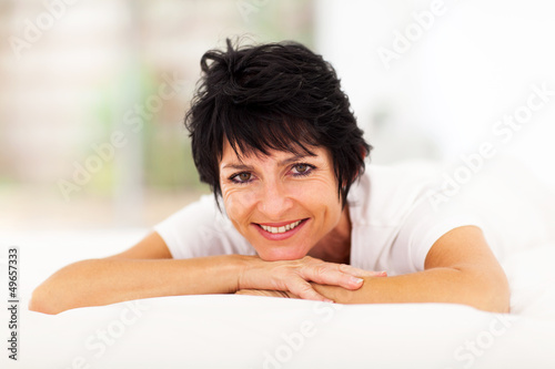 pretty mid aged woman lying on bed at home