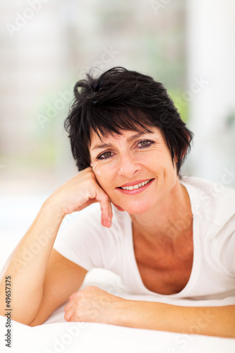 attractive middle aged woman lying on bed at home