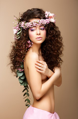 Sultry Beauty. Naked Woman - Long Curly Hair, Wreath of Flowers