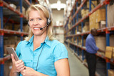 Businesswoman Using Headset In Distribution Warehouse
