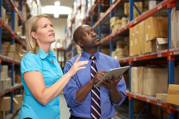 Businesspeople With Digital Tablet In Warehouse