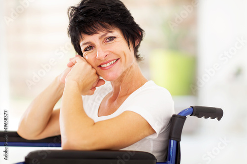happy disabled middle aged woman sitting on wheelchair