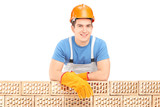 Male construction worker resting on a brick wall