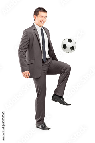 Full length portrait of a young handsome businessman kicking a f