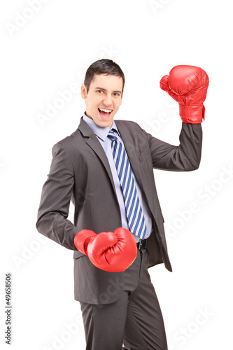 Happy young businessman with red boxing gloves