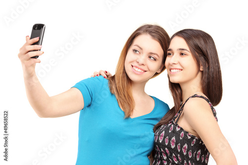 Two happy teenagers taking pictures of themselves with a cell ph