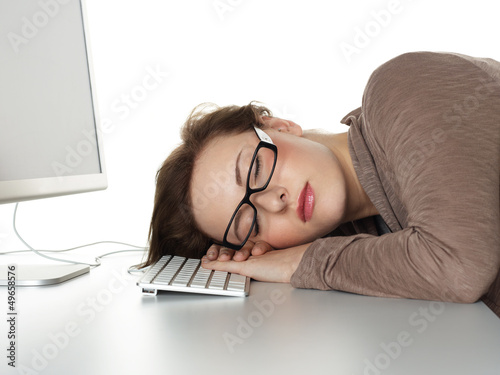 Business woman sleeping on her keyboard at work