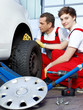 Car mechanics check the tread pattern of a winter tire