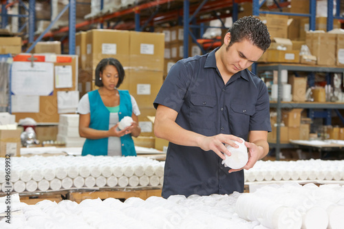 Factory Worker Checking Goods On Production Line - 49659932