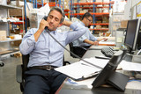 Businessman Working At Desk In Warehouse