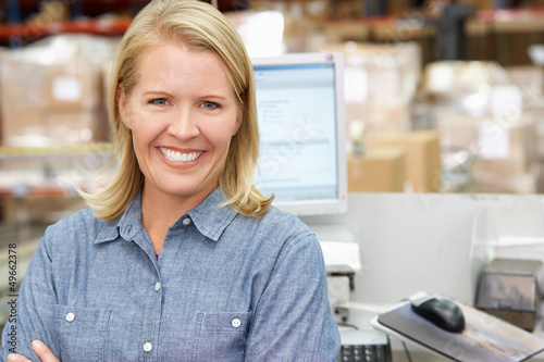 Woman At Computer Terminal In Distribution Warehouse