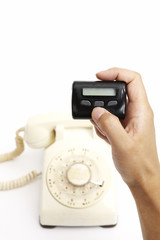 Old landline telephone and human hand holding pager