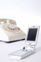 Old landline telephone and mobile phone, close up