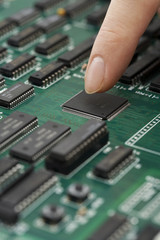 Finger touching chip on green circuit board, close up