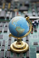 Globe on green circuit board, close up