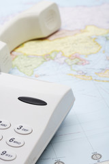 Landline phone receiver off the hook on a world map
