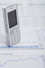 Mobile phone standing on a financial report