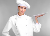Portrait of young woman chef with tray on grey background