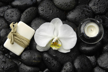 White orchid and candle with soap on zen stones background