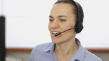 Attractive helpdesk consultant talking on headset, close up