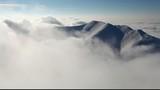 Big mountain over clouds form in a valley - time lapse video