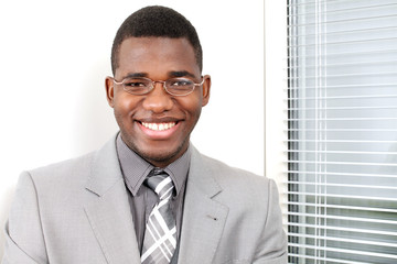 Business smile, young man by office window