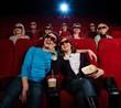 Group of people in 3D glasses watching movie in cinema