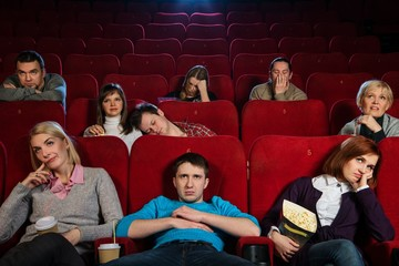 Group of boring people watching movie in cinema