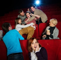 Fight between young men happening in cinema during film show