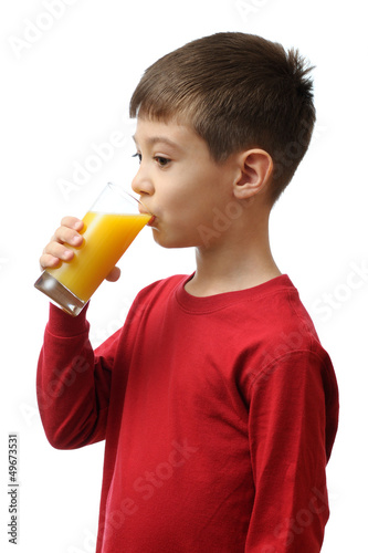 Child drinks orange juice isolated on white background