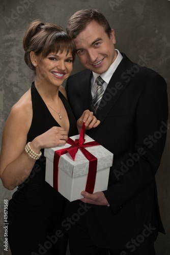 Young smiling man and woman with gift box