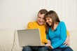 Smiling man and woman with laptop sitting on sofa