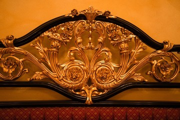 Back of expensive sofa with golden ornament
