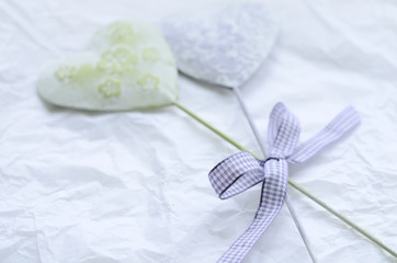 Tender green and lavender decorative hearts on light background
