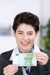 glückliche frau hält 100 euro in der hand
