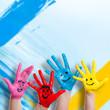 lachende Kinderhände vor Farbwand