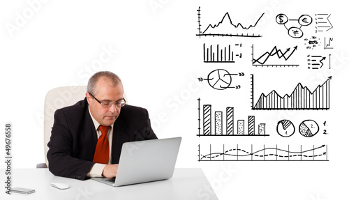 Businessman sitting at desk with diagrams and laptop