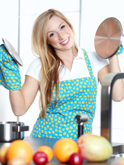 Happy baking cooking woman in her kitchen with lids