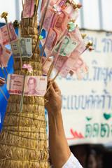 Hand put thai banknote in make merit
