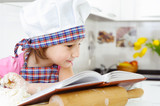 Little baker in hat preparing cookies with cookbook