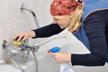 Junge Frau putzt Armaturen