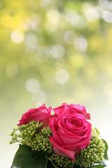strauss mit rosen vor frühlingsbokeh