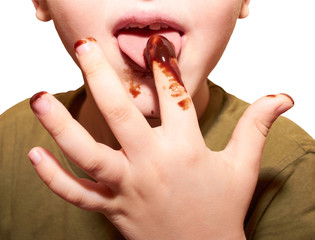 Child licks a chocolate glaze with your finger