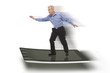Senior businessman keeping balance on a PC tablet