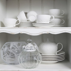 pure white cup  with plate , standing in white cupboard