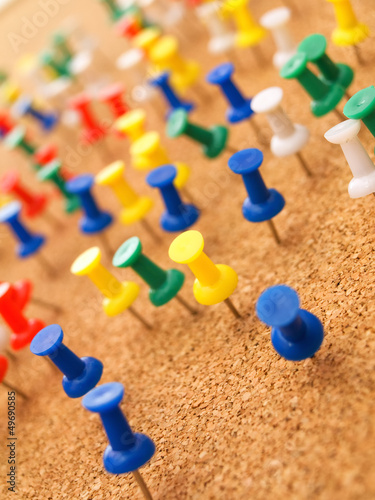Colorful thumbtacks on cork board